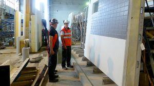 Lujabetonin työntekijät tarkastelevat valmista elementtiseinää