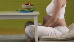 Odottava äiti terveellisen aterian ääressä.