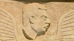 Viiksekkäät kasvot kiveen veistettynä.