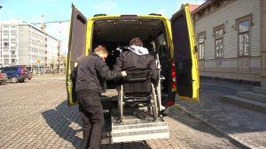 Palveluliikennöitsijä auttaa pyörätuolilla liikkuvaa miestä alas taksista.