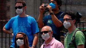 Hengityssuojaa käyttäviä turisteja Meksikon pääkaupungissa Méxicossa