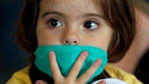 Pikkutyttö piteli hengityssuojaa kasvoillaan saavuttuaan Sao Paulon lentokentälle Brasiliaan Meksikosta 29. huhtikuuta.