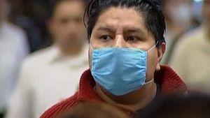 Meksikolaismies kävelee ruuhkassa hengityssuojain kasvoillaan.