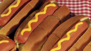 Hot dogeja rivissä punavalkoruutuisen pöytäliinan päällä.