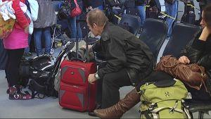 Matkustajia istumassa lentoasemalla.