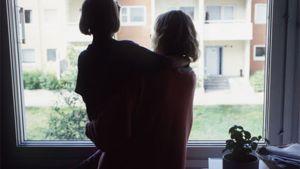 Äiti katsoo lapsi sylissään ulos ikkunasta.