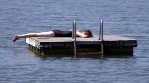 Nainen ottaa aurinkoa laiturilla.