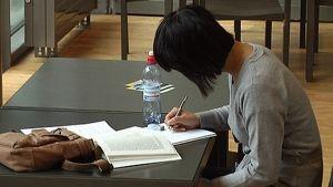 Naisopiskelija istuu pöydän ääressä ja lukee kirjaa sekä tekee muistiinpanoja. Pöydällä laukku ja vesipullo.