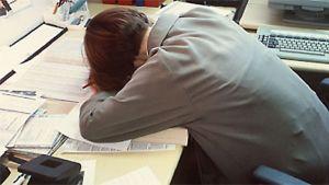 Kuvassa nainen on tuupertunut työpöydän päälle.