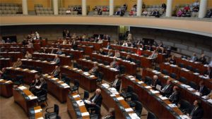 Eduskunnan istuntosali ja parvi, kansanedustajia paikoillaan istunnon aikana ja yleisöä parvella.