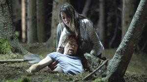 Nainen kohottaa maahan kaatunutta miestä hartioista.