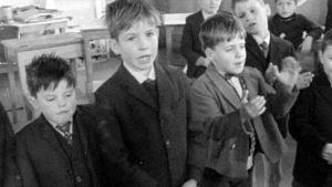 Poikia laulamassa irlantilaisessa poikakodissa.