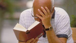 Kalju mies lukee kirjaa puistonpenkillä.