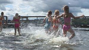 Uimakoululaiset juoksevat veteen.