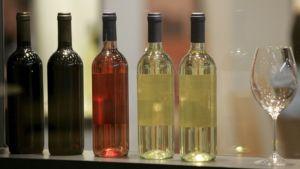 Viinipulloja rivissä ja lasi.