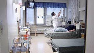 Sairaanhoitaja vaihtaa potilaan tiputuspussia sairaalahuoneessa.