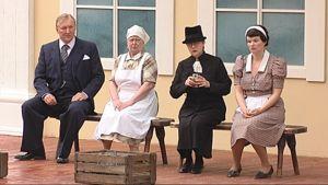 Näyttelijät istuvat penkillä näytelmän harjoituksissa.
