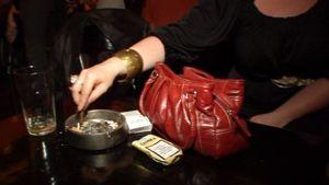 Nainen tumppaa sikarin tuhkakuppiin ravintolan pöydässä.