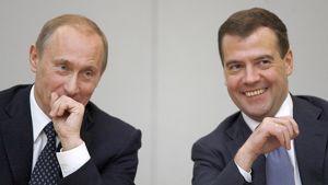 Vasemmalla istuva Vladimir Putin pitää kättään suunsa edessä ja oikealla istuva Dmitri Medvedev hymyilee.