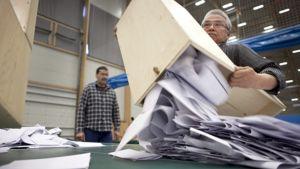 Vaalivirkailija tyhjentää vaaliuurnan.