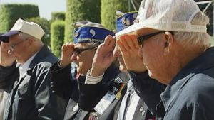 Joukko amerikkalaisia sotaveteraaneja kohottaa kätensä lippaan tervehdyksen merkiksi.