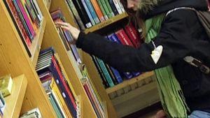 Tyttö valitsee kirjan kirjaston hyllystä.
