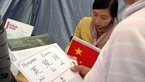 Kiinankielen opettaja kääntää vieressä seisovien tyttöjen nimiä kiinaksi