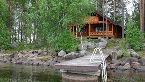 Kuvassa hirsinen huvila kivikkoisella järvenrannalla kesäisessä maisemassa, etualalla laituri.