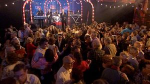 Ihmisiä lavatansseissa, yhtye soittaa lavalla.