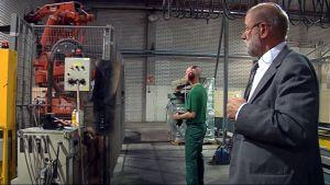 Miehet katsovat robotin toimintaa vaneritehtaalla.