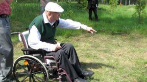 Mannerheimristin ritari Onni Määttänen osoittaa pyörätuolistaan, mihin vielä on syytä lisätä multaa katajan juurelle.