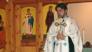 Pastori Mikko Sidoroff jumalanpalveluspuvussa kirkon ikonostaasin edessä.