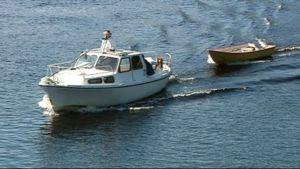 Valkoinen vene ajaa joella hinaten soutuvenettä.