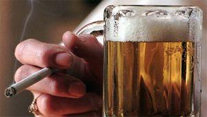 Kuvassa oluttuoppi ja savuketta pitelevä käsi.