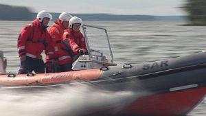 Järvipelastajien vene kiitää vedessä.