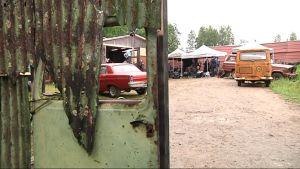 Lavasteita, kuten vanhoja autoja hallin pihalla.