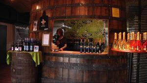 Viinitilan tynnyrin muotoinen myyntiluukku ja paljon pulloja.