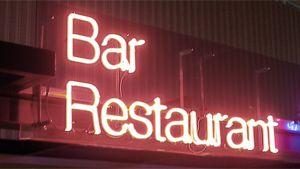"""Ravintolan julkisivun punainen neonvalokyltti, jossa sanat """"Bar Restaurant""""."""
