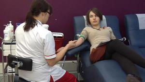 Nuori nainen luovuttaa verta.