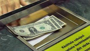 Dollareita rahanvaihtopisteen teräksisessä palvelu-uurnassa.