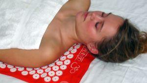 Nainen makaa piikkimatolla