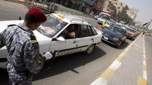 Bagdadilainen poliisi tarkastamassa autoja.