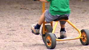 Lapsi ajaa kolmipyöräisellä pihalla.