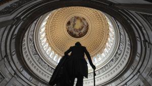 Kongressi kokoontuu Capitol-rakennuksessa, jonka rotunda kuvassa kaartuu Georg Washingtonin patsaan silhuetin yläpuolella.