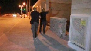 Kaksi miestä yöllä rakennuksen vierellä, toinen osoittaa sisälle taskulampulla.