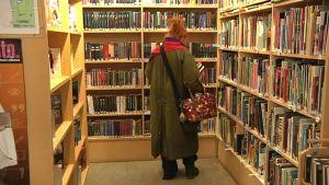 Lainaaja kirjaston hyllyjen äärellä