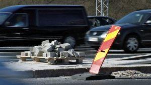 Autoja menee ohi liikennetyömaan. Keskipiennarta laatoitetaan kivillä.