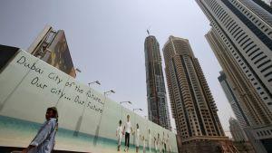 """Aasialainen työläinen kävelee leveän julistemainoksen ohi, jossa lukee: """"Dubai City of the future... Our City... Our Future""""."""