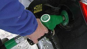 Mies tankkaa bensiiniä autoon.