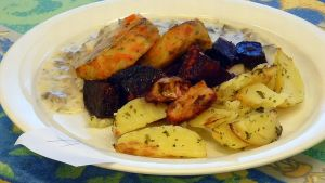 Ruoka-annoksessa yrttiset lohkoperunat punajuurilisäkkeellä sekä kasvispihvejä sienikastikkeella.